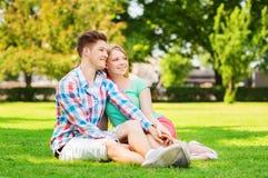 Pares sonrientes que se sientan en hierba en parque Imágenes de archivo libres de regalías