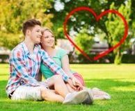 Pares sonrientes que se sientan en hierba en parque del verano Imagenes de archivo