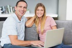 Pares sonrientes que se sientan usando el ordenador portátil en el sofá junto Imagen de archivo