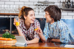 Pares sonrientes que sonríen y que usan la tabla junto en cocina Foto de archivo libre de regalías