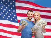 Pares sonrientes que sostienen el dinero del efectivo del dólar Fotografía de archivo libre de regalías