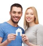 Pares sonrientes que sostienen la casa del Libro Blanco Fotos de archivo