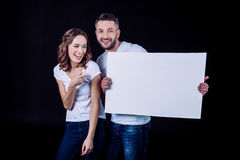 Pares sonrientes que sostienen la tarjeta en blanco fotos de archivo libres de regalías