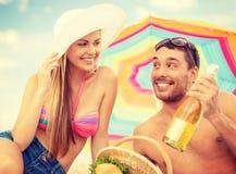 Pares sonrientes que tienen comida campestre en la playa Fotos de archivo libres de regalías