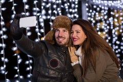 Pares sonrientes que toman el selfie con el teléfono elegante en la pista de hielo Foto de archivo