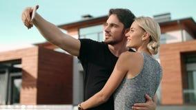 Pares sonrientes que toman el selfie fuera de la casa de lujo Retrato de pares preciosos almacen de video