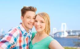 Pares sonrientes que toman el selfie sobre el puente Imagen de archivo