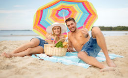 Pares sonrientes que toman el sol en la playa Fotografía de archivo libre de regalías