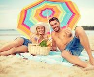 Pares sonrientes que toman el sol en la playa Imagen de archivo libre de regalías