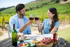 Pares sonrientes que tuestan las copas de vino rojas mientras que se sienta en la tabla Foto de archivo