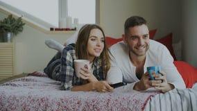 Pares sonrientes que ven la TV mientras que miente en cama y que beben el café en casa por la mañana metrajes