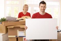 Pares sonrientes rodeados con los rectángulos en nueva casa Imágenes de archivo libres de regalías