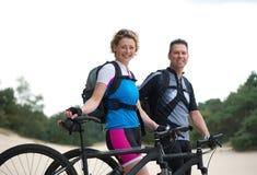 Pares sonrientes sanos que se colocan con sus bicis al aire libre Imagen de archivo libre de regalías