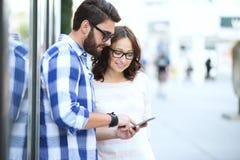 Pares sonrientes usando el teléfono elegante junto en ciudad Fotografía de archivo libre de regalías