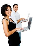 Pares sonrientes usando las computadoras portátiles Imagen de archivo libre de regalías