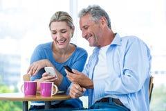 Pares sonrientes usando los teléfonos móviles en el café Fotografía de archivo libre de regalías