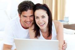 Pares sonrientes usando una computadora portátil que miente en su cama Foto de archivo