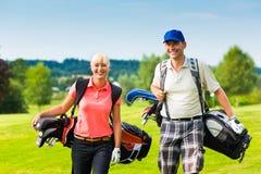 Pares sportive novos que jogam o golfe em um curso foto de stock royalty free