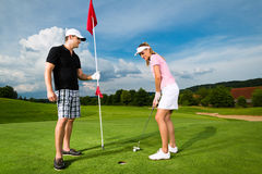 Pares sportive novos que jogam o golfe em um curso fotografia de stock