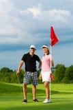 Pares sportive novos que jogam o golfe em um curso imagem de stock