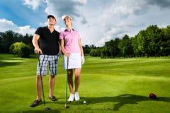 Pares sportive novos que jogam o golfe em um curso imagens de stock