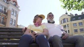 Pares superiores à moda que relaxam no banco na cidade vídeos de arquivo