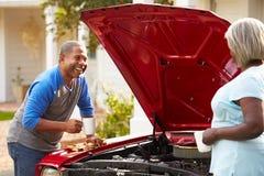 Pares superiores aposentados que trabalham no carro restaurado foto de stock
