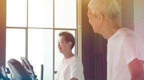 Pares superiores asiáticos felizes que correm no estilo de vida saudável da escada rolante foto de stock royalty free