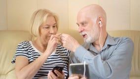 Pares superiores bonitos alegres que sentam-se no sofá Música de escuta no smartphone com fones de ouvido filme