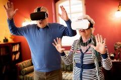 Pares superiores chocados engraçados usando vidros da realidade virtual Foto de Stock