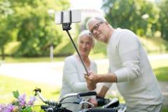 Pares superiores com as bicicletas que tomam o selfie no parque fotografia de stock royalty free