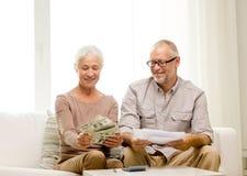 Pares superiores com dinheiro e calculadora em casa Fotografia de Stock Royalty Free