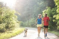 Pares superiores com o cão que corre na natureza ensolarada verde Imagens de Stock