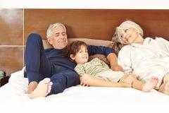 Pares superiores com os netos na cama Imagens de Stock Royalty Free