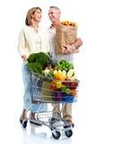 Pares superiores com um carro de compras na mercearia. Imagens de Stock Royalty Free