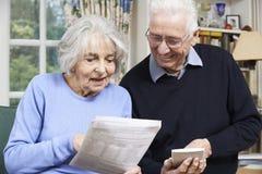 Pares superiores em casa com as contas que verificam em casa finanças Imagens de Stock Royalty Free