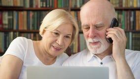 Pares superiores em casa com portátil Família aposentada dos pensionista que usa o telefone que discute o smth na tela filme