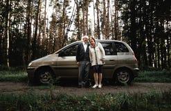 Pares superiores felizes com carro novo fotografia de stock