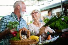 Pares superiores felizes com a cesta no mercado local imagem de stock royalty free