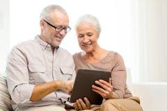 Pares superiores felizes com PC da tabuleta em casa Imagens de Stock Royalty Free