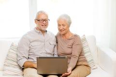 Pares superiores felizes com portátil em casa Fotos de Stock