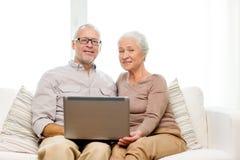 Pares superiores felizes com portátil em casa Fotografia de Stock