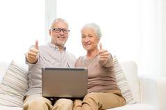 Pares superiores felizes com portátil em casa Foto de Stock