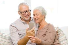 Pares superiores felizes com smartphone em casa Fotografia de Stock