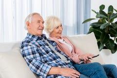 Pares superiores felizes com a tevê de observação de controle remoto imagem de stock royalty free