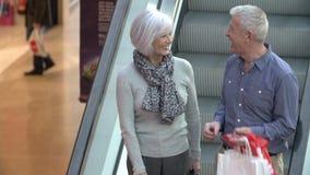 Pares superiores felizes na escada rolante no shopping vídeos de arquivo