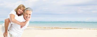 Pares superiores felizes na praia. Imagem de Stock