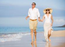 Pares superiores felizes na praia. Aposentadoria Res tropical luxuoso imagem de stock