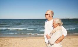 Pares superiores felizes que andam ao longo da praia do verão Imagem de Stock