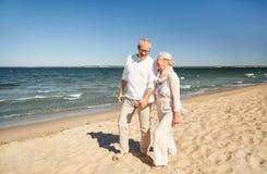 Pares superiores felizes que andam ao longo da praia do verão Foto de Stock